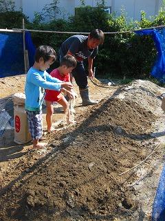 畑に肥料をやる園児達
