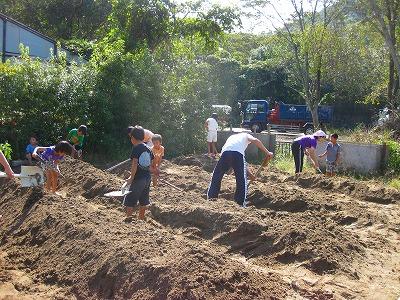 畑で作業する先生と園児達